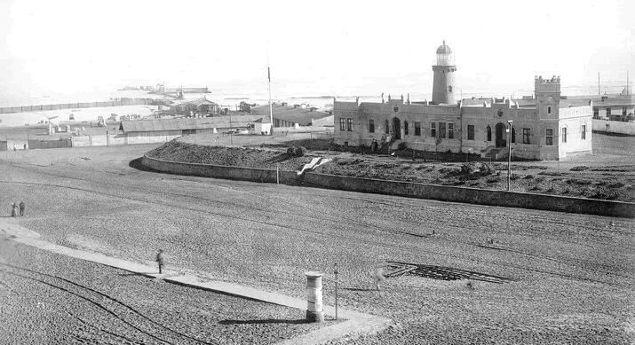 The lighthouse and the district office (Bezirksamt) in 1905 overlooking the pier (Mole) and harbour cranes for unloading shipments.