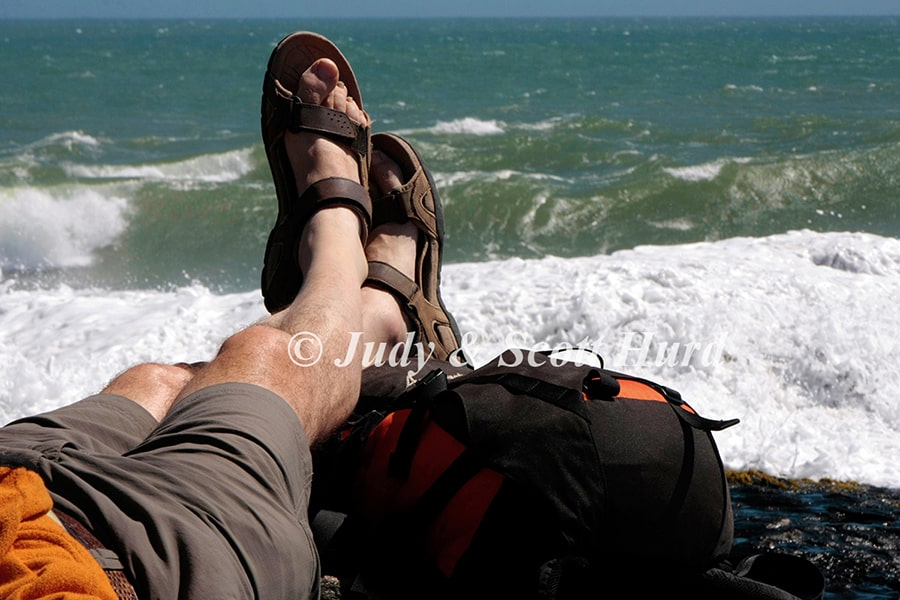 """""""A walker rests his feet on his rucksack as the waves roll in"""" Rights to Judy & Scott Hurd"""