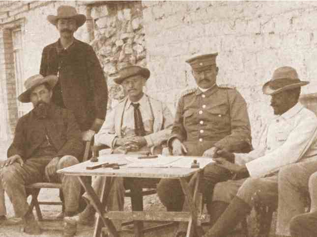 Signing of agreement between governor Leutwein, commandant Lombard (left), Dr Hartmann (2nd f.l.) and Samuel Maharero (right); standing translator Kleinschmidt; Grootfontein, 1895. Photo Collection: National Archives of Namibia